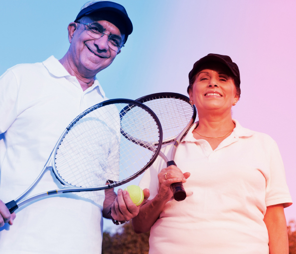 Smiling couple holding tennis raquets